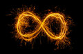 Infinity symbol glowing moebius strip isolated on black background Stock Images