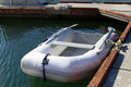 Inflatable boat attached to pier in bay water Royalty Free Stock Photo