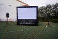 Inflatable outdoor movie screen with audio sound system professionally setup on a field for an event measures ft diagonally and Stock Photo