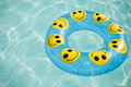 Inflatable water ring pool toy with smiley faces Stock Image
