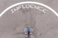Influence text on asphalt ground, feet and shoes on floor Royalty Free Stock Photo