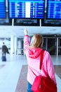 Information in airport young woman pointing on flight Stock Photo