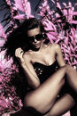 Infrared fashion model with sunglasses in black top and bikini leaves in background Royalty Free Stock Images