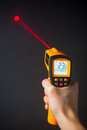 Infrared laser thermometer in hand black background Royalty Free Stock Photo
