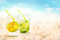 Infused water lemon and cucumber in mug on sea sand beach summer day and nature background Royalty Free Stock Photo