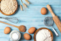 Ingredients for baking, milk, eggs, wheat flour, oats and kitchenware on blue wooden background, top view