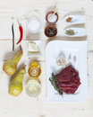 Ingredients for beef tenderloin with vanilla and candied pears on a wooden board Stock Images