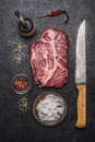 Ingredients for cooking beef steak with salt and pepper  carving knife, pepper mill on a dark rustic background top view Royalty Free Stock Photo