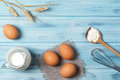 Ingredients for cooking, milk, eggs, wheat flour and kitchenware on blue wooden background, top view Royalty Free Stock Photo