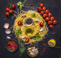Ingredients for cooking pasta with tomato on a branch, oil, garlic and pepper, egg on wooden rustic background top view close up Royalty Free Stock Photo