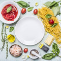 Ingredients for cooking pasta, tomatoes in own juice, basil, shrimp, grater, cherry tomatoes, laid around a white plate place Royalty Free Stock Photo