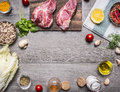 Ingredients for cooking pork steak with vegetables, fruits, spices, laid out by frame,place text on wooden rustic background