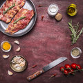 Ingredients for cooking raw lamb ribs in a pan with herbs, a knife, seasoning, tomatoes place for text,frame on wooden rustic back Royalty Free Stock Photo