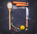 Ingredients for cooking rice with vegetables, a knife, a wooden spoon, lemon, spicy, pepper, garlic lined frame with text area on Royalty Free Stock Photo