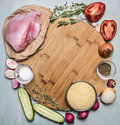 Ingredients for cooking turkey breast with couscous with vegetables and spices on a cutting board round on wooden rustic backgroun Royalty Free Stock Photo