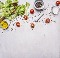 Ingredients for cooking Vegetarian Food, lettuce, cherry tomatoes, oil, salt and pepper wooden rustic background top view close Royalty Free Stock Photo