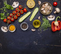Ingredients for cooking vegetarian food tomatoes on a branch, herbs, cucumber, lemon, garlic, oil, black pepper, paprika, mushroom Royalty Free Stock Photo
