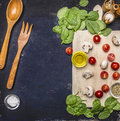 Ingredients for cooking vegetarian meal, mushrooms, spinach and cherry tomatoes with wooden spoon fork for the salad, place fo Royalty Free Stock Photo