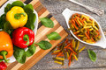 Ingredients for a delicious fusilli pasta with an overhead view of fresh colofrul sweet bell peppers in red yellow and orange on Royalty Free Stock Photo