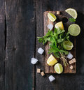 Ingredients for ice green tea lime lemon mint sugar and cubes on wooden chopping board over old wooden background Stock Photo