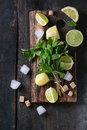 Ingredients for ice green tea lime lemon mint sugar and cubes on wooden chopping board over old wooden background Stock Photography