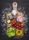 Ingredients for risotto with ham, vegetables and spices on a cutting board on wooden rustic background top view close up Royalty Free Stock Photo