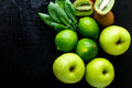 Ingredients for smoothie. Green fruits on black wooden background. Apple, lime, spinach, kiwi. Detox. Healthy food. Top view. Copy Royalty Free Stock Photo