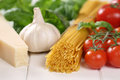 Ingredients for a spaghetti pasta noodles meal with tomatoes ba basil and parmesan cheese Royalty Free Stock Photo