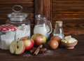 Ingredients and tools for baking - flour, eggs, butter, apples, cinnamon on a brown rustic wooden surface. Royalty Free Stock Photo