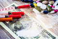 Injection syringe with cocaine drug powder and pills, dollar Royalty Free Stock Photo