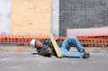 Injured construction worker at work site a fallen and in a hard hat laying on the ground a Royalty Free Stock Image