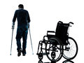 Injured man with crutches walking away from wheelchair silhou one in silhouette studio on white background Stock Photo