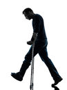 Injured man walking sad with crutches silhouette one in studio on white background Stock Image
