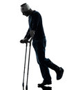 Injured man walking sad with crutches silhouette one in studio on white background Stock Photos