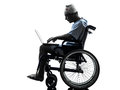 Injured man in wheelchair computing laptop computer silhouette one studio on white background Royalty Free Stock Photo