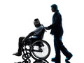 Injured man in wheelchair with nurse silhouette one men sleeping studio on white background Stock Images