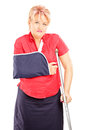 Injured mature woman with broken arm and crutch isolated on white background Stock Photography