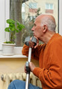 Injured old man with crutch Stock Image