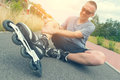 Injured skater with painful leg sitting and holding his Royalty Free Stock Photo