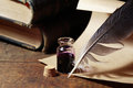 Inkpot and quill pen vintage still life with feather near scroll books Stock Image