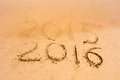 Inscription 2015 and 2016 on a beach sand, the wave is starting to cover the digits 2015 Royalty Free Stock Photo