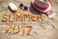 Inscription summer 2017, accessories for sunbathing and passport with currencies euro on sand at beach, summer time