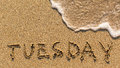 Inscription TUESDAY on a gentle beach sand with the soft wave