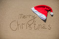 Inscription on the wet sand and cap of Santa Claus Royalty Free Stock Photo