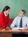 Insegnante felice with little girl che discute allo scrittorio Immagine Stock