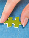 Inserting the last yellow piece of puzzle in free space in assembled jigsaw puzzles Royalty Free Stock Images