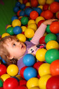 Inside the ball pit little girl having fun on an indoor playground in an activity centre Stock Images