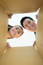 Inside the box positive young people looking into a cardboard Royalty Free Stock Photo