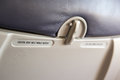 Inside flight airoplane seat focusing with the warning label of fasten seat belt Royalty Free Stock Image