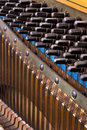 Inside an upright piano felt hammers used to strike steel strings and wound knobs to tune Royalty Free Stock Photo